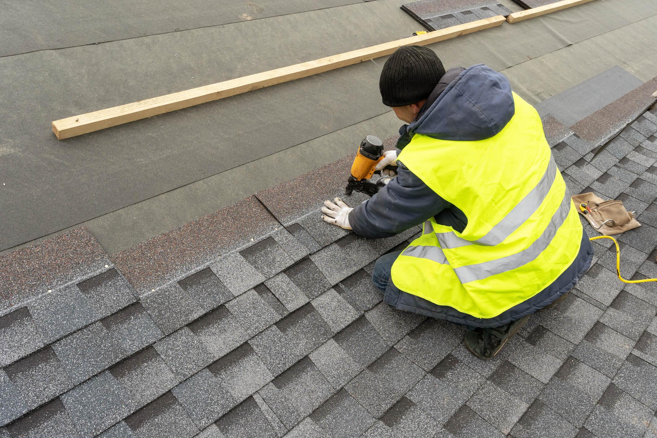 roof repairman installing shingle